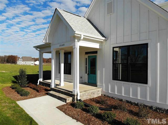 The Rodanthe is finished with board and batt exterior with black windows, stone accents, painted in Sherwin Williams SW-7005 Pure White, constructed by custom home builder near Chapel Hill NC