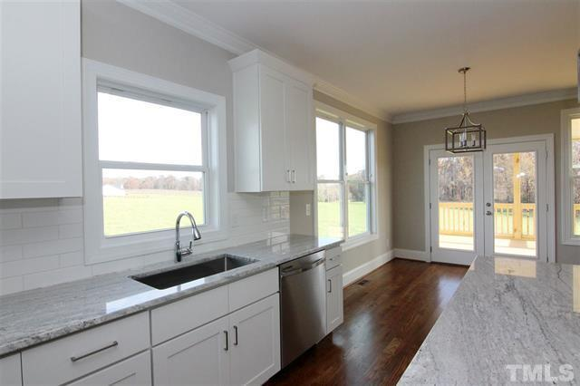 Large window at Kitchen Sink.  Oversized white subway tile, Thunder White granite, white cabinets, Minwax Provincial floor stain.  Built near Chapel Hill by Travars Built Homes.
