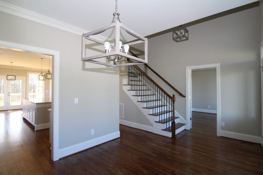 Formal Dining Room across from Office, off Foyer.  Modern Farmhouse lighting fixtures, Minwax Provincial floor stain color, oak staircase, Sherwin Williams 7043 Worldly Gray paint color.  Built by custom home builders Travars Built Homes in Pittsboro NC