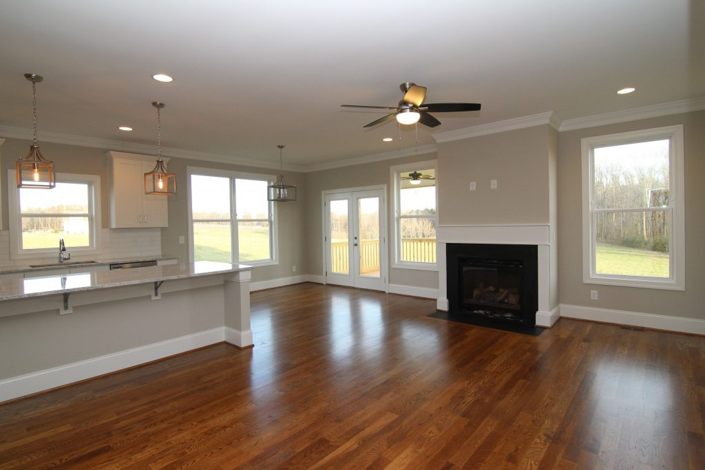 Great Room in the Rodanthe, with Minwax Provincial stain on site-finished hardwoods, SW-7043 Worldly Gray wall color.  Built by Travars Built Homes near Pittsboro NC.