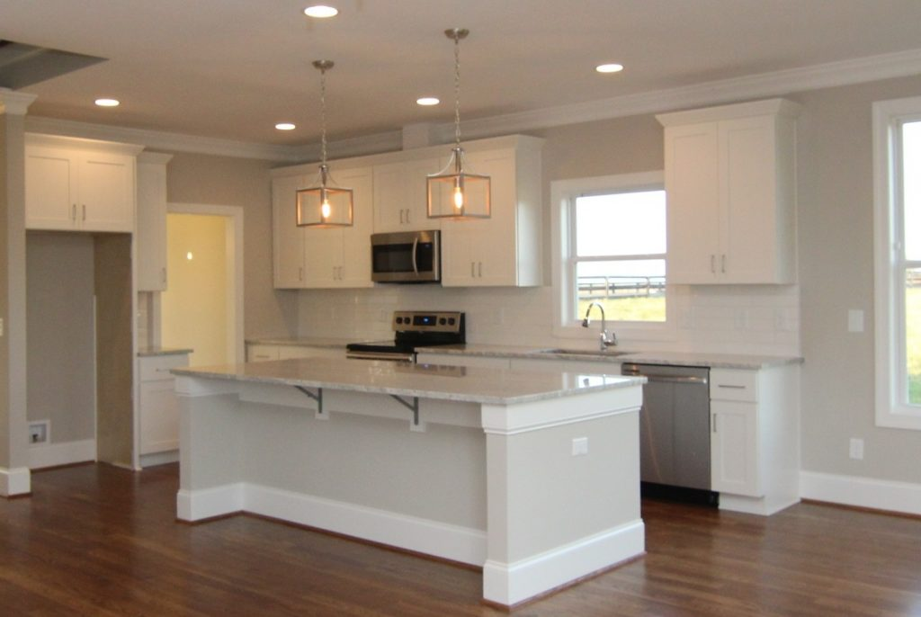 Island with seating for four.  Thunder white granite, Minwax Provincial floor stain, white cabinets and white subway tiles.  Built in Chatham County by custom home builders Travars Built Homes.