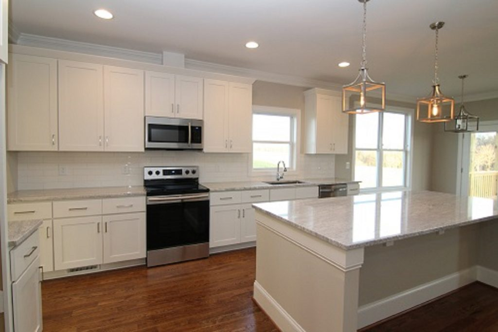 Plenty of counter space in the Rodanthe kitchen.  Thunder White granite, SW-7043 Worldly Gray Paint, Minwax Provincial stain color, 4x12 white subway tile.  Chapel Hill builders Travars Built Homes.